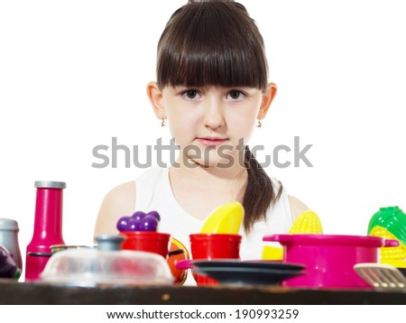Small caucasian girl child cooking with toys tableware isolated on white - stock photo
