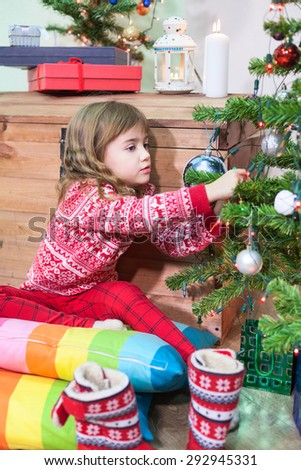 Small Caucasian girl decorates the Christmas tree with toys in domestic room - stock photo