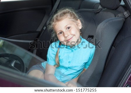 Small Caucasian girl in car safety seat going to journey - stock photo