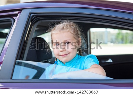 Small Caucasian girl looking at camera from car window - stock photo