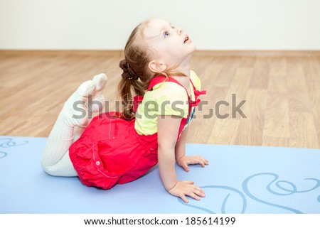 Small Caucasian girl making yoga pose on mat in gym - stock photo