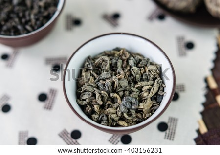 Small ceramic bowl with dry green tea leaves on Japanese pattern tablecloth, close up - stock photo