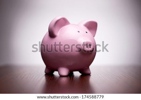 Small ceramic pink piggy bank with vignetting, conceptual of money, finances, retirement and saving for your dreams and goals - stock photo