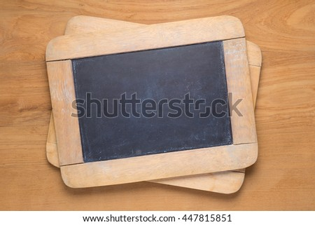 Small chalk blackboards on wooden desk, empty with room for copyspace text - stock photo