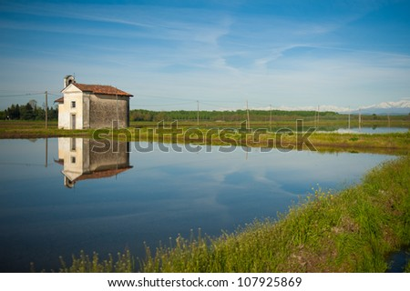 Small chapel and wet rice field in the Vercelli region of Italy - stock photo