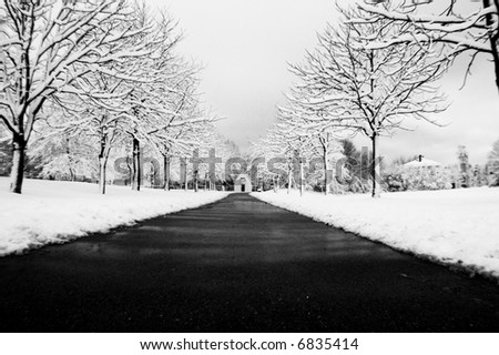 Small chapel at the end of a long dark path in a winter scene - stock photo