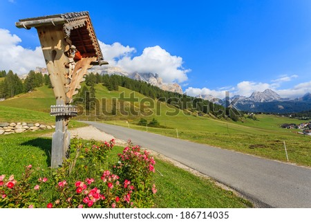 Small chapel in flowers on alpine meadow by the road, San Cassiano, South Tirol, Dolomites Mountains, Italy - stock photo