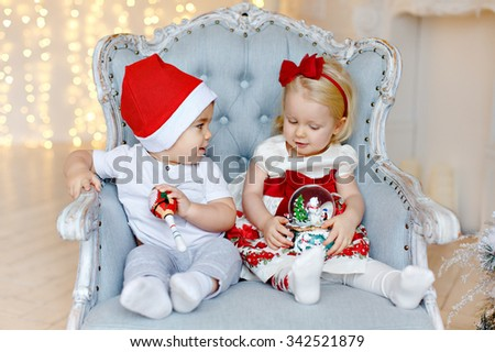 Small charming baby boy in red Santa hats and the little blond girl sitting in a chair against a background of Christmas lights in the interior of the house - stock photo