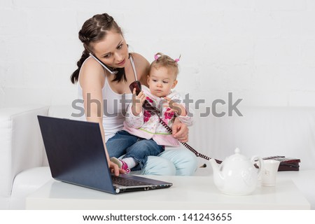 Small child and busy young woman with notebook and phone sit on the sofa in the room. - stock photo