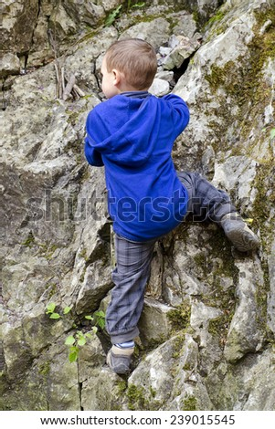 Small child boy climbing and scrambling a rock in a nature. - stock photo