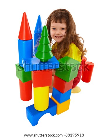 Small child built a castle from color cubes isolated on white background - stock photo