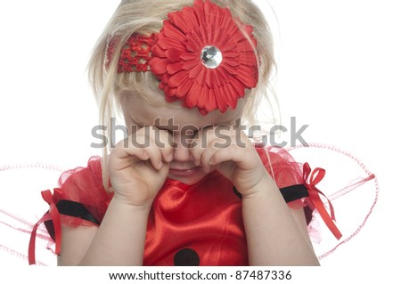 Small child dressed as a lady bird and has sad expression and is rubbing her eyes,. the girl aslo has a red flower in her hair