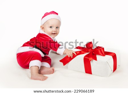 small child dressed as Santa Claus.  Kid with Christmas gift