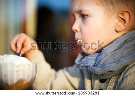 Small child eating ice cream, portrait of little boy - stock photo