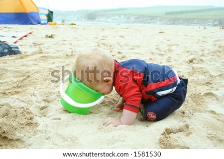 Small child exploring a beach in Cornwall. - stock photo