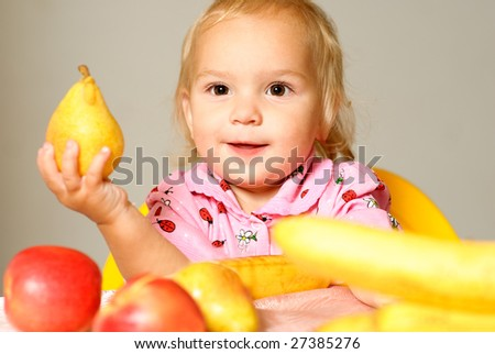 Small child holds big pear in hand. - stock photo