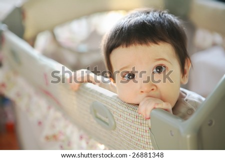 small child in baby-child's bed, soft focus - stock photo