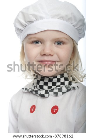 small child is dressed a chef, it is a close up and she is smiling