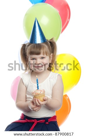 small child is holding a cupcake in her hand. the child is smiling and looking directly at camera