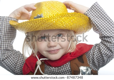 small child is holding her yellow had. the child is dressed in a cowgirl costume