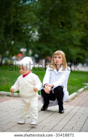 Small child learns to go independently. In park. - stock photo