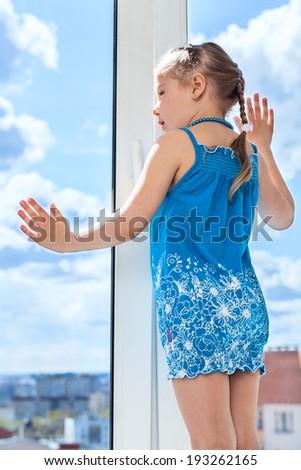 Small child looking through window, standing on windowsill - stock photo
