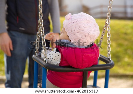 Small child on a swing on the playground - stock photo