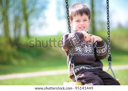 Small child on swing in playground outdoors