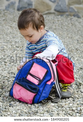 Small child or toddler opening his backpack or bag  while crouching on the ground. - stock photo