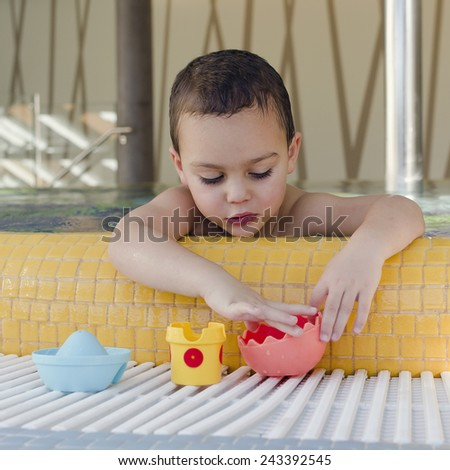 Small child playing in a shallow children swimming pool with toys.