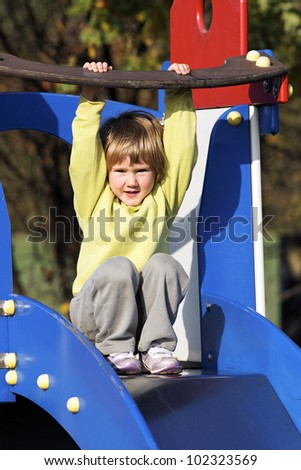 Small child playing on colorful playground - stock photo