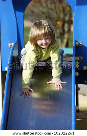 Small child playing on colorful toboggan - stock photo