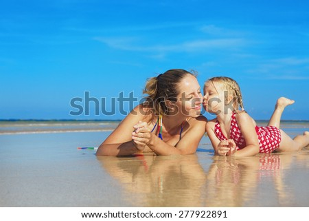 Small child playing with fun and kissing happy young mother smiling with love to her daughter lying on wet sand sea beach. Family lifestyle and summer vacation with children on tropical island resort - stock photo