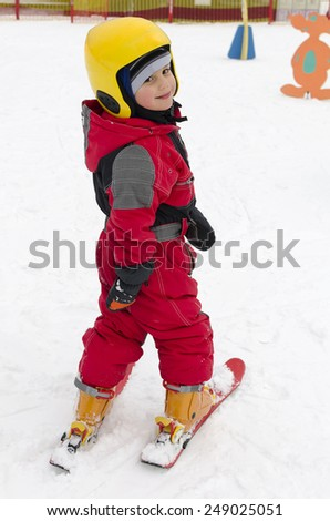 Small child skier learning skiing on a ski slope.