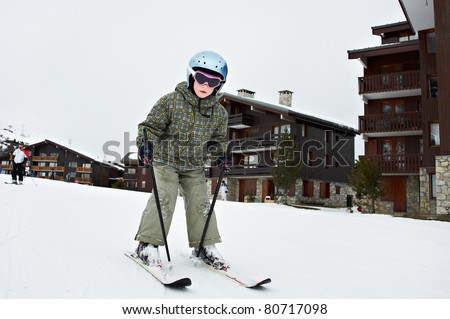 Small child skiing in French resort on background wooden chalet