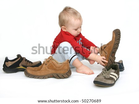 Small child tries to put on his father's shoes. Baby boy with big shoes in hand isolated on white. - stock photo