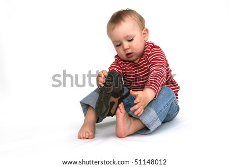 Small child tries to put on his shoes. Baby boy with shoes in hand isolated on white. - stock photo