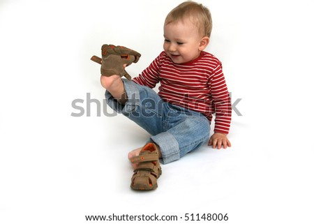 Small child tries to put on his shoes. Baby boy with summer shoes in hand isolated on white.