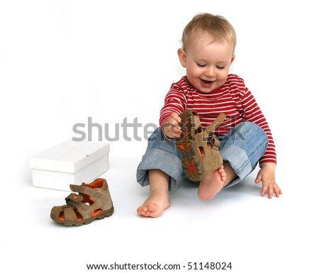 Small child tries to put on his shoes. Baby boy with summer shoes in hand isolated on white. - stock photo