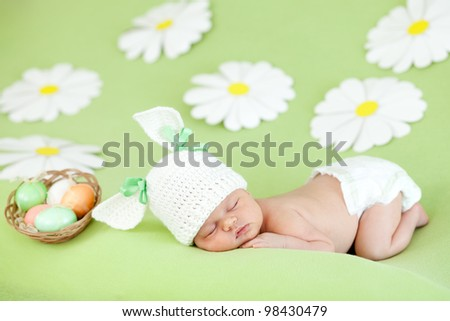 small child with a rabbit ears. Lying on his stomach with Easter eggs in basket - stock photo