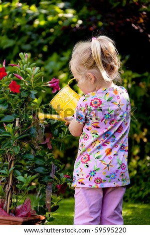 Small child with a watering can with flowers pour