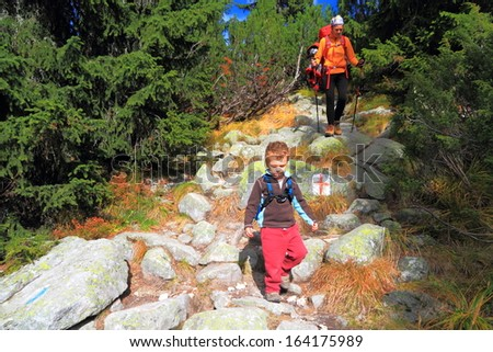 Small child with his mother hike on the mountain trail - stock photo