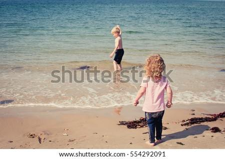 Small children exploring the sea and beach whilst on vacation