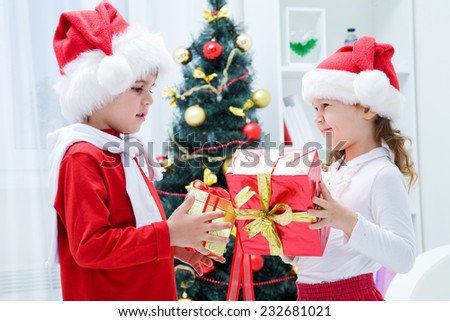 small children give gifts at Christmas - stock photo