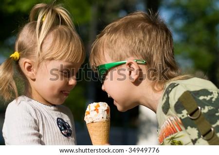 Small children in a summer garden eat cold icecream - stock photo