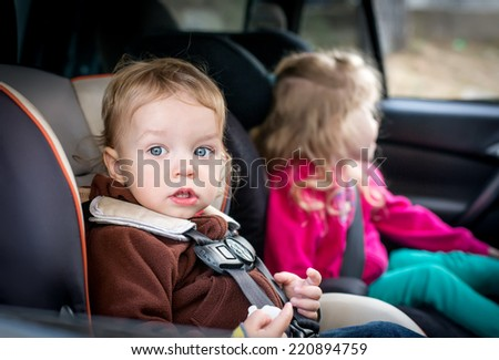 small children in car seats in the car - stock photo