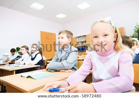 Small children sit in desks