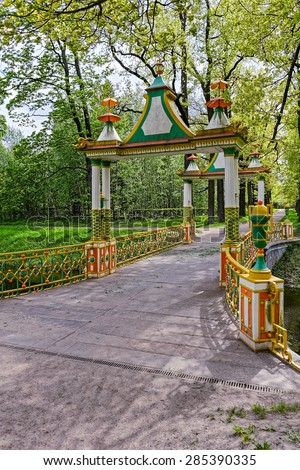 Small chinese bridge over canal with multicolored decoration - stock photo
