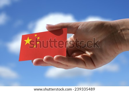 Small Chinese flag against sky with cumulus clouds - stock photo