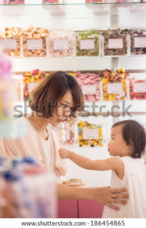 Small Chinese girl feeding her mother with a sweet in a candy shop - stock photo